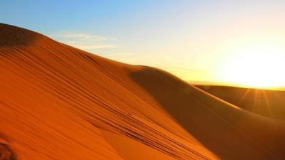 sun setting on a hill of red sand in the Sahara Desert
