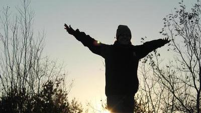 silhouette of a person with arms outstretched in front of the setting sun