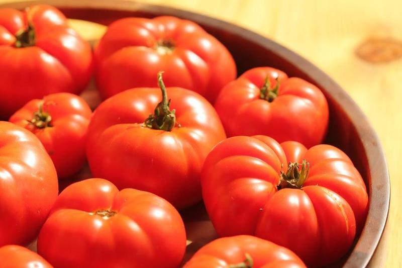 big beautiful red tomatoes in a wooden bowl