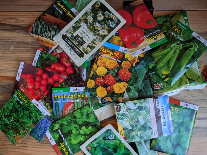 a pile of packets of seeds for flowers, herbs, and vegetables