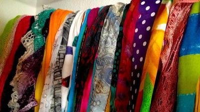 A row of colorful scarves hanging in a closet