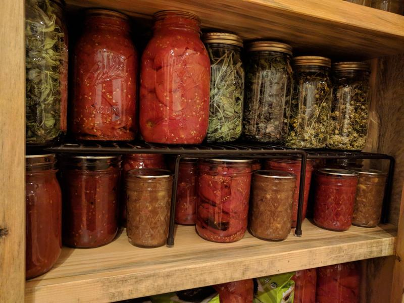 jars of roasted tomatoes, jams, and herbs in a wooden cupboard