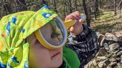 toddler holding a magnifying glass up to her eye and looking up at the sky