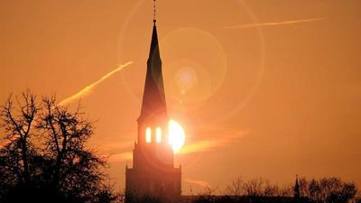 the sun rises behind the steeple of a church