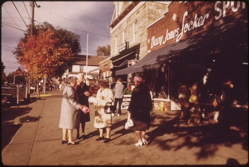 a few older women standing on a sidewalk outsie of some shops in the downtown of a small town