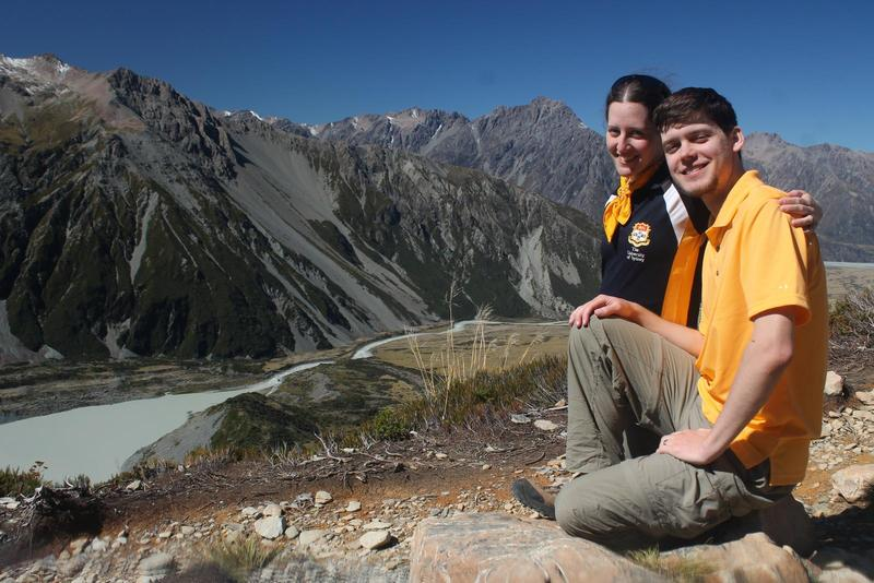 Randy and Jacqueline sit on a mountain in New Zealand