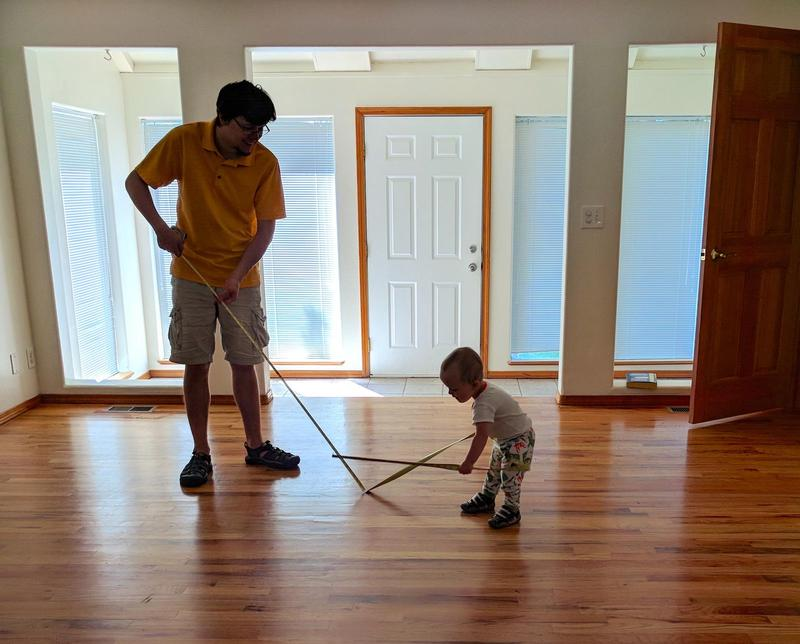 Randy and his toddler son measuring an empty room with a tape measure as sunlight streams in the window onto the hardwood floors