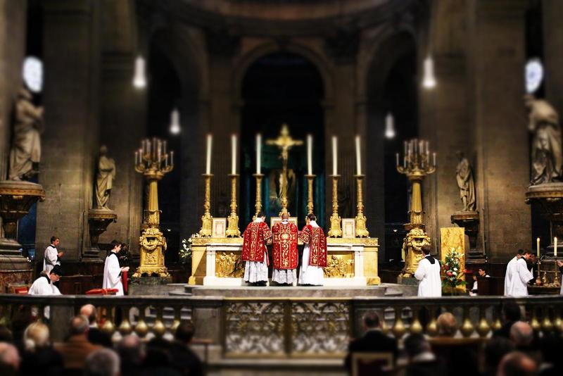 Priests in red and gold celebrate a traditional Latin Mass