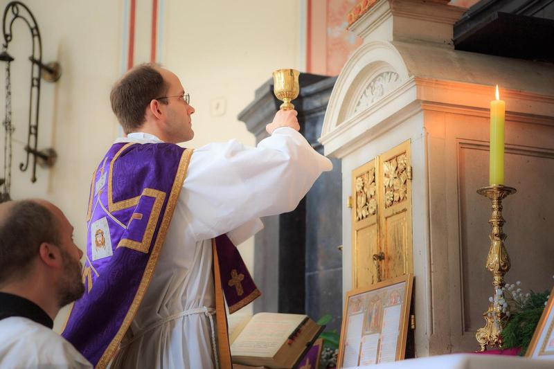 A Catholic priest in purple and gold holds up a chalice in front of an altar