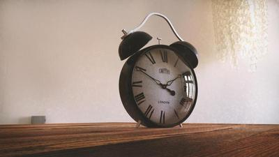 old fashioned alarm clock sitting on a wood table