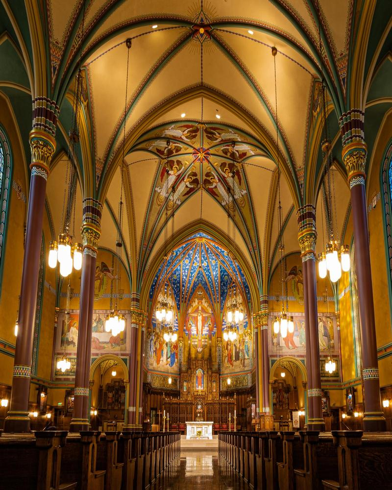 inside of the Cathedral of the Madeleine in Salt Lake City, with beautiful arches, paintings, and gold tim