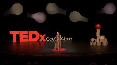 Jacqueline standing on a red carpet circle on stage in front of big letters saying TEDx Couer d'Alene
