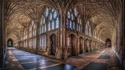 the cloisters at gloucester cathedral: the intersection of two long stone hallways lined with windows, stained glass, and elaborate archways